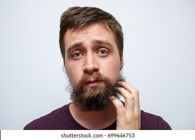 Confused and uncertain man scratching messy beard