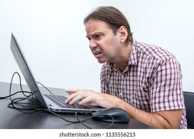 The confused unhappy user is looking at the computer screen. Surprised stressed man looking at laptop. System error on computer.