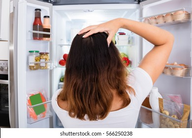 Confused Woman Near Refrigerator