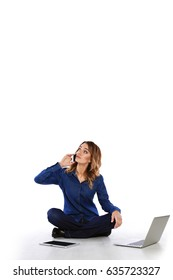 Confused woman talking on the phone while sitting on the floor with a tablet and a laptop on a white background