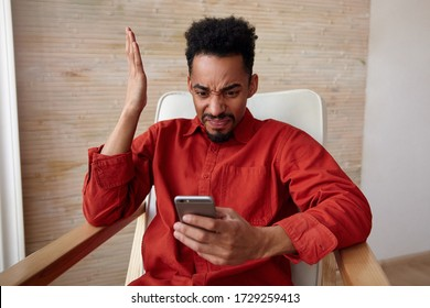 Confused young bearded dark skinned male with short haircut grimacing his face and keeping hand raised while looking on his smartphone with pout, posing over beige background