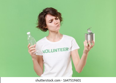 Confused young brunette woman in volunteer t-shirt isolated on pastel green wall background. Voluntary free work assistance help charity grace teamwork concept. Hold trash empty plastic bottle tincan