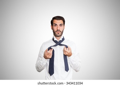 Confused young business man holding his untied tie.