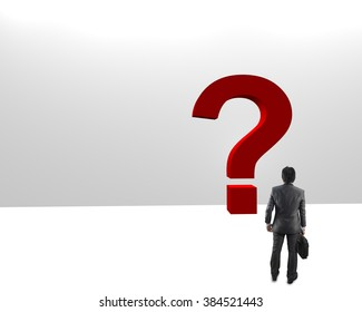 Confused, young businessman looking at red question marks