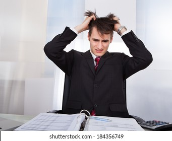 Confused young businessman pulling hair while calculating finances at desk in office