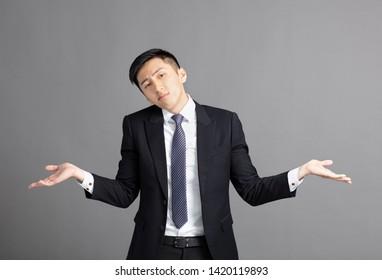 confused young businessman shrugging shoulders