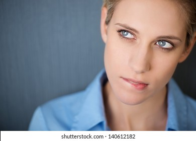 Confused young businesswoman biting lip while looking away against grey wall