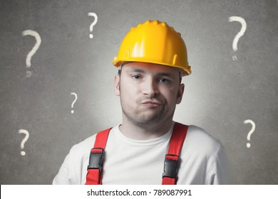 Confused young handyman with question marks