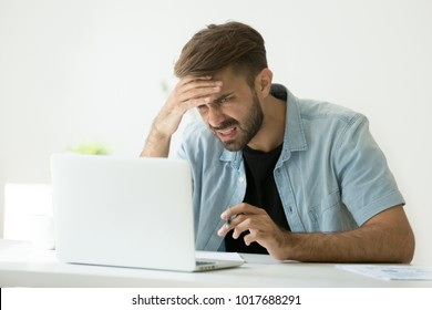 Confused young man frustrated by online problem looking at laptop screen, worker troubled doing hard job on computer making notes, student feels stressed about difficult learning failing test or exam