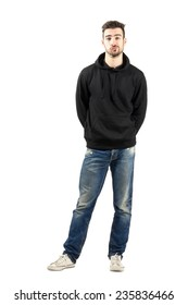 Confused young man in hoodie with hands on back. Full body length portrait isolated over white background.