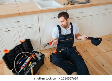 Confused young man sit on floor in kitchen and look at toolbox. He hold wrench. Tired man has rest.