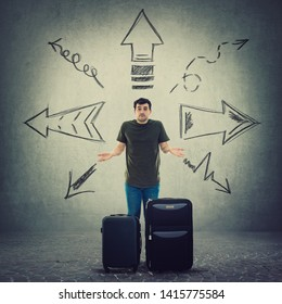 Confused young man traveler standing behind his luggage don't know where to go. Perplexed tourist guy has problems to choose vacation destination way as arrows pointed to different directions.