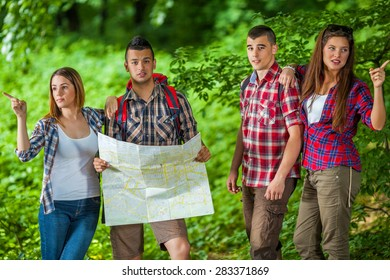 Confused young men with map looking at camera and confident young women showing them directions in the forest