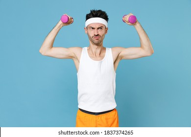 Confused young strong sporty fitness man with thin skinny body sportsman in white headband shirt shorts doing exercise with dumbbells isolated on blue background. Workout gym sport motivation concept