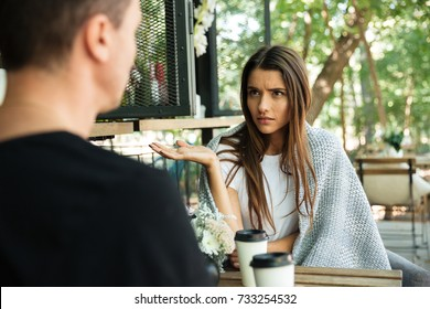 Confused young woman gesturing with hand and looking at her boyfriend while sitting in a cafe at the park outdoors