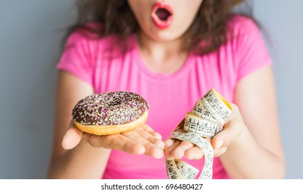 Confused young woman holding a donut and a measuring tape. Concept of Sweets, Unhealthy Junk Food and obesity.