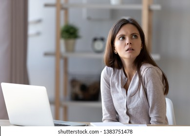 Confused young woman sit at office home desk working at laptop look at clock realizing missing deadline, frustrated disappointed girl feel puzzled late for appointment, forget meeting or gathering