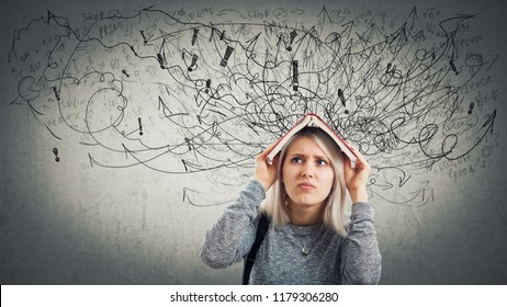 Confused young woman student holding a opened book over head. Stressed emotion, unhappy feeling, difficult task to solve. Hundreds of arrows and curves mess, anxiety and headache.