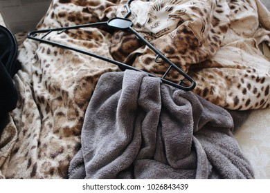 Confusion on the bed. Broken clothes. A crumpled blanket, a hanger, a carpet. Chaos. Fast morning.