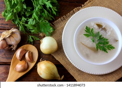 congee in ceramic bowl on rustic wooden table, traditional rice porridge typical of Asian cuisine. Top view