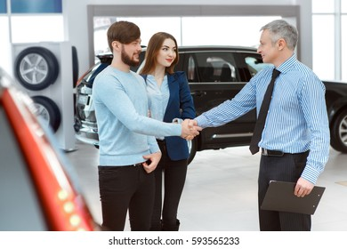 Congrats! Professional mature salesman shaking hands with young handsome man car dealer selling a new car to a happy couple rental deal agreement seller buyers customers clients buying car business
