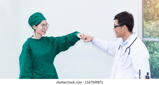 Congratulate and cheerful. Senior handsome researcher and young beautiful woman medical studen greeting to work.Doctor in white suit and glasses.Female in green suit.Copy space.