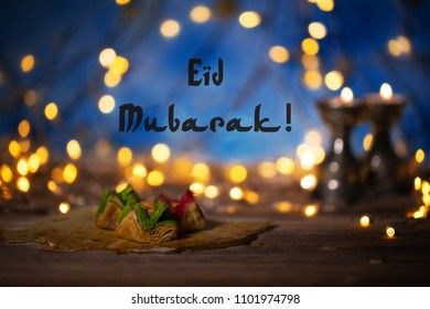 Congratulation: Eid Mubarak! Arabic sweets on a wooden surface. Candle holders, night light and night blue sky with crescent moon in the background.
