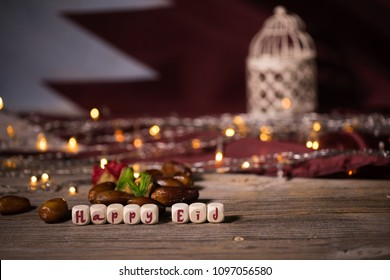 Congratulation HAPPY EID composed of wooden dices. Flag of Qatar in the background.