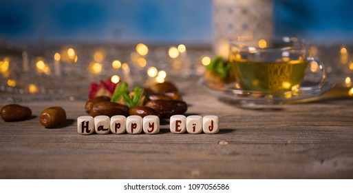 Congratulation HAPPY EID composed of wooden dices. Cup of green tea and dates in the background