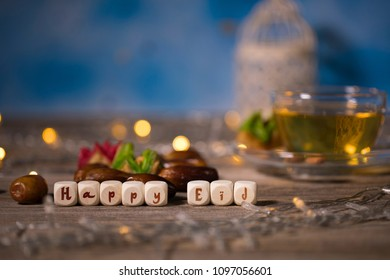 Congratulation HAPPY EID composed of wooden dices. Dates and cup of green tea in the background.