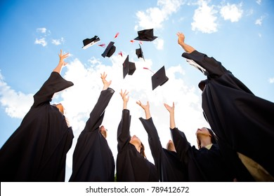 Congratulations! Low angle view of happy group of six young cheerful graduates in black gowns, throwing up their head wear in the air and celebrating, in blue summer sky, laughing, enjoying