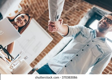 Congratulations! Low angle view of two men shaking hands while their coworker sitting at the table in office