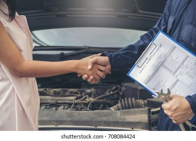 Congratulations. young businesswoman shaking hands with Mechanic the car dealer in auto show after a successful deal.