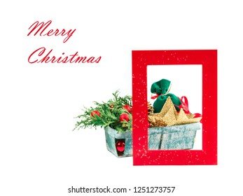 """Congratulatory inscription in red color """"Merry Christmas"""" on the white isolated background. A box with New Year's toys, a fir-tree and a bag with gifts against the background of a red frame for a phot"""
