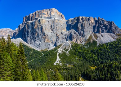 The coniferous forests. Majestic white and gray rocks against the blue sky. The most beautiful route in the Italian Dolomites. The concept of active and car tourism
