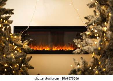 Coniferous trees with fairy lights placed near wall with electric fireplace on Christmas day at home