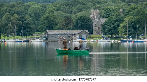 Coniston, Cumbria, UK. July 2020.  2 fisherman in a boat on Coniston water
