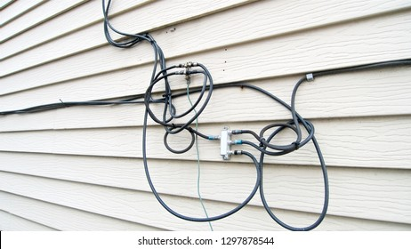 Connected cables and wirings on a house siding for home internet, phone and television cable service subscription service.