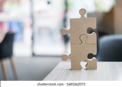 connecting couple puzzle over table with copy space for text,  wood jigsaw inside office. Business solutions, mission, target, success, goals and strategy concepts