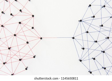 Connecting networks concept - two network connected with yarn red and blue on white paper. Simulator connection social media, internet, people communication