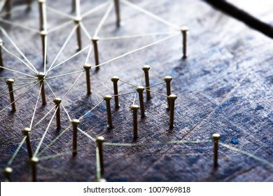 Connecting people and devices. Networking, social media, SNS, internet infrastructure communication abstract. Small or private network connected to a social network. Web of gold wires on rustic wood.
