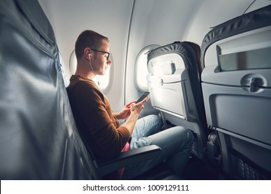 Connection in the airplane. Young man (traveler) using smart phone during flight and listening music.