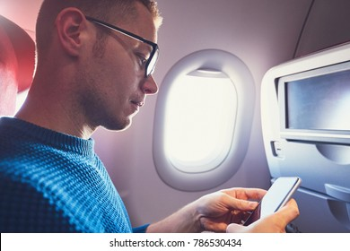 Connection in the airplane. Young passenger (traveler) using smart phone during flight.