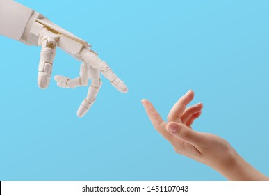 Connection between people and artificial intelligence technology. Female hand and robot reaching to each other on blue