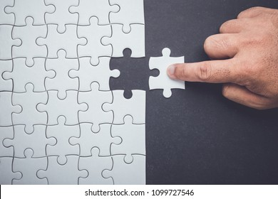 Connection concept : Hand holding pieces of jigsaw puzzle and insert into the missing hole