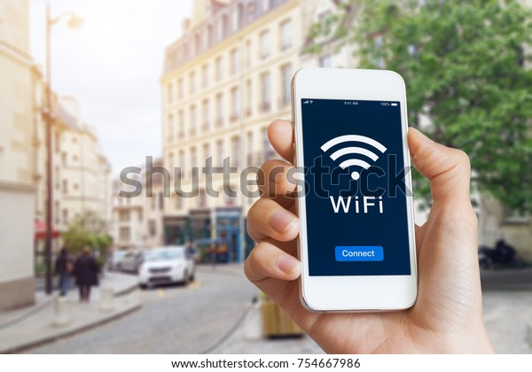 Connection to public WiFi hotspot in the city street to access internet on smartphone, concept about wireless technology and travel, close-up of hand