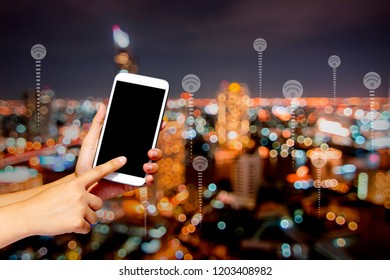 Connection and technology concept, holding phone and press on screen on night city background