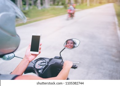 Connection technology and transport. Young woman in helmet holding smartphone while driving motobike. Copy space on the screen.