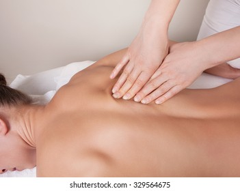 Connective tissue massage on  a muscle group (erector spinae muscles) of a woman's back