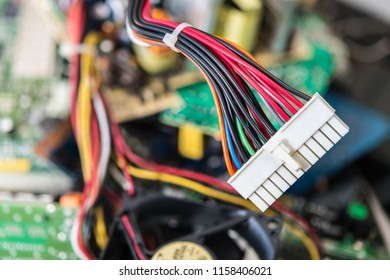 Connector with power cables for computer mainboard. Colorful blurry background from PC components. Small depth of field. Idea of electronics industry, eco, sorting and disposal of electronic waste.
